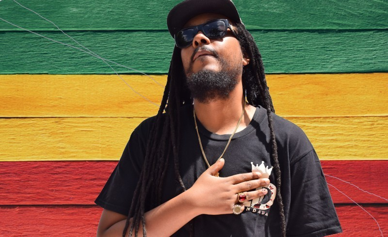 Don Dada holding left hand to chest reggae colours background
